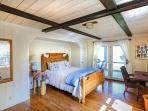 Large queen bedroom with sliding door to deck. Shares a bathroom with another guest room.