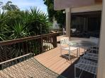 Westerly facing deck with lounging chairs and barbecue grill.