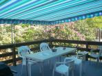The back deck with gas grill, outdoor table and chairs under a beautiful awning