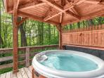 Covered, private hot tub with a beautiful view up in the trees.