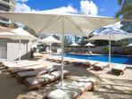 Sun lounges around heated outdoor swimming pool.