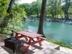 Picnic table and BBQ grill on the banks of the Guadalupe River.