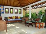 The living area is surrounded by tropical gardens.