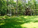 Side yard - volleyball area; hammock and treehouse in background
