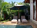 Sun beds beside the pool are shaded with a large umbrella.