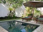 The pool had daybeds beside it shaded by a large umbrella.