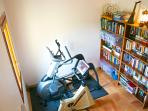 Gym with exercise bikes and elliptical machine and library with English books and toys