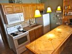 A full kitchen with oven, stovetop, microwave, fridge and tons of cookware allow you to prepare your own meals as if...