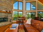Living area has leather sofas, gas log fireplace and 2-story windows with mountain views.