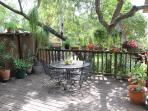 The large deck surrounded by plants. We have yet another table plus chairs for 8