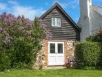 THE OLD WORKSHOP, pet-friendly, character holiday cottage, with a garden in