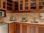 Kitchenette, equipped with microwave, fridge, utensils, and kettle.
