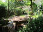 Un coin repas du jardin sous une tonnelle de Glycine.