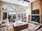 Living area with wood burning fireplace,  50' flat screen TV and access to the large wrap around deck.