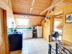 The wood-panelled loft has a good sized kitchen diner withe fitted kitchen to one end and a table and four chairs
