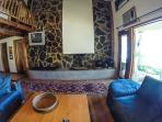 Sala a doble altura con tapanco y chimenea con muro de piedra volcánica.