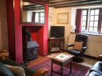 Sitting room, leather twin settees and log burning stove. Kindling and logs provided