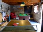 Games room showing the dart board, badminton rackets and cricket bat. There is also an extra fridge