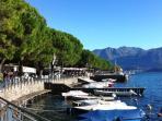 The Tuseday water-front market in Lenno looking towards the lake-ferry 'Navigazione' jetty