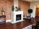 Great room with exposed brick wall, rough cut granite gas fireplace,