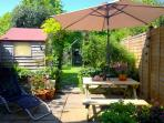 Edible herbs, log shed on left, first arch leads onto lawn with swing seat, grape vine, roses, shubs
