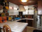 Amplia cocina equipada. Tiene extractor de aire, microwave y refrigerador. Trastes y closet-despensa