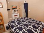 Bedroom with queen bed and vanity