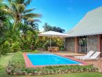 Oversized swimming pool with lounge chairs and sundeck,umbrella to complete Fijian experience