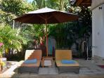 The sun lounges are shade by a large umbrella.