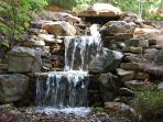 Beautiful waterfall beside our Deck with Gas Fire Pit and Weber Gas Grill.