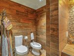 The full bathroom features unique wood-paneled walls.