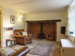 A cosy wood burning stove and comfortable leather seating in the sitting room
