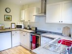 Kitchen - electric double oven/grill and hob, fridge with freezer, microwave, dishwasher, utensils