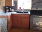A view of the kitchen with a granite sink and ceramic top stove with a convection oven.
