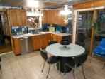 Eat-in kitchen with custom cabinets, quartz tops, glass backsplash,
