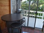 The sunroom has a pub table with four chairs and is just off the kitchen.  Above hangs a large fish.