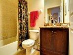 Guest bathroom has shower / tub combo.