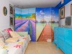 biombos colorados que separad la dos camas individuales de el saloncito television