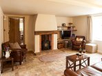 The sitting room has exposed oak beams, leather seating and a cosy woodburning stove