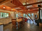 Main floor of cabin is cozy yet open with kitchen, dining and living space