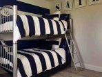 Nautical room with twin bunk beds (top bed is mounted and can be brought down and placed side by side)