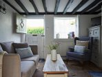 A stable door leads to a cosy sitting room with low ceilings and beams. Not suitable for tall people