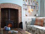 The comfortable living room features a log burner and plenty of books, puzzles and games.