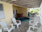 Large verandah with Jacuzzi, lots of seating and lounging chairs and hammock