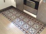 Raffinement dans la cuisine avec ce tapis de sol représentant des carreaux de ciment anciens.
