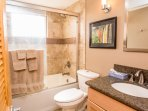 The tiled Second Bath has a deep tub with shower. There is a maple vanity and granite counters.