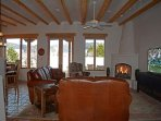 Entering living room with sweeping mountain view window wall, jumbo flat screen satellite TV, gas log fireplace + large...