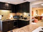 Full granite kitchen has stove, dishwasher, refrigerator, microwave.