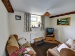 The compact sitting room has a small but comfortable three piece suite
