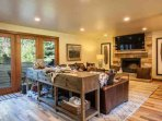 Living room with gas fireplace, large flat screen smart TV, deck access and comfortable yet stylish furnishings.